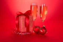Weihnachtsgeschenke, Spielwaren, Serpentin und Weingläser Lizenzfreie Stockfotografie