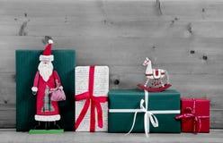 Weihnachtsgeschenke und Geschenkboxen mit Sankt auf grauer hölzerner Rückseite Stockbild