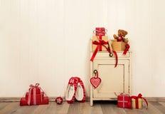 Weihnachtsgeschenke und Geschenke in den roten und weißen Farben auf altem Holz Stockfotografie