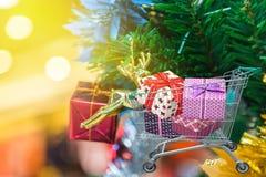 Weihnachtsgeschenke und -geschenke im Einkaufslaufkatzenwarenkorb mit Weihnachtsdekorationen und Weihnachtsbaumhintergrund Stockbild