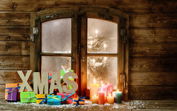 Weihnachtsgeschenke und Kerzen-Lichter am Fenster Lizenzfreie Stockfotos