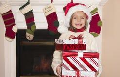 Weihnachtsgeschenke und kleines Mädchen Stockfotos