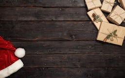 Weihnachtsgeschenke und Sankt-Hut auf Holztisch Stockbild