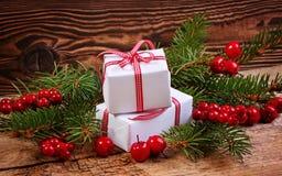 Weihnachtsgeschenke verziert mit Kiefernbürsten und roten Beeren Stockbilder