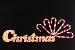 Weihnachtsgestreifte Stocksüßigkeiten auf Schwarzkiefer Stockfotografie