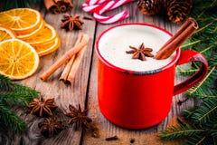 Weihnachtsgetränk: Eierpunsch mit Zimt und Anis im roten Becher Stockfoto