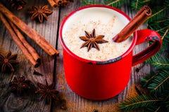 Weihnachtsgetränk: heiße weiße Schokolade mit Zimt und Anis im roten Becher Stockfotos