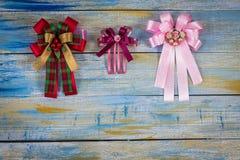 Weihnachtsgewebebogen auf farbigem hölzernem Hintergrund Lizenzfreies Stockfoto