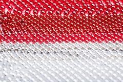 Weihnachtsgirlande hergestellt von den kleinen roten und silbernen Perlen, Nahaufnahme Stockfoto