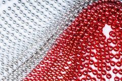 Weihnachtsgirlande hergestellt von den kleinen roten und silbernen Perlen, Nahaufnahme Lizenzfreie Stockbilder