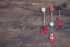 Weihnachtsgirlande mit roten hölzernen Rotwild, Herzen, Weihnachten-Baum und Kegeln Dunkler Hintergrund Schneeflocken Lizenzfreie Stockfotos