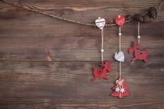 Weihnachtsgirlande mit roten hölzernen Rotwild, Herzen, Weihnachten-Baum und Kegeln Dunkler Hintergrund Schneeflocken Stockbilder
