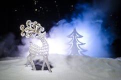 Weihnachtsgirlanden in der Baumform und in der Zahl eines Rotwilds auf der Straße während Schneefälle Lizenzfreie Stockfotos