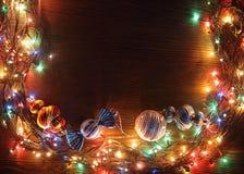Weihnachtsgirlanden von Lampen auf einem hölzernen Hintergrund Stockfotografie