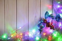 Weihnachtsgirlanden von Lampen auf einem hölzernen Hintergrund Stockfoto