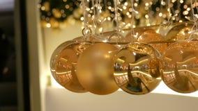 Weihnachtsgirlandenlichter und Bälle der Goldfarbe mit einem unscharfen Hintergrund Dekor des neuen Jahres und des Weihnachten in stock video footage