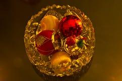 Weihnachtsglänzende farbige Dekorationen in einer Glasschüssel Lizenzfreie Stockfotografie