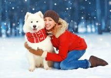 Weihnachtsglückliche lächelnde Frau, die Spaß mit weißem Samoyedhund auf Schnee im Wintertag hat lizenzfreies stockfoto