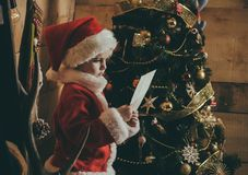 Weihnachtsglückliches Kind gelesener Wunschbrief stockfotografie