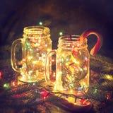 Weihnachtsglühende Glasgefäße mit glänzenden Girlanden und Zuckerstange mit Kiefernniederlassungen in der Dunkelheit Stockbild