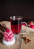 Weihnachtsglühwein im Glas mit rotem Hut Lizenzfreie Stockfotografie