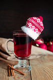 Weihnachtsglühwein im Glas mit rotem Hut Lizenzfreies Stockfoto