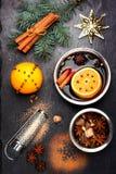 Weihnachtsglühwein mit Gewürzen auf schwarzer Schiefertafel Stockfotos