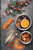Weihnachtsglühwein mit Gewürzen auf schwarzer Schiefertafel Lizenzfreies Stockfoto