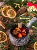 Weihnachtsglühwein mit Zimt-, Orangen- und Sternanis in einer keramischen Schüssel mit Winterdekorationen stockfoto