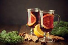 Weihnachtsglühwein in zwei Gläsern auf hölzernem Hintergrund mit Orange, Zimt, Sternanis und Kiefer verzweigt sich Stockfoto