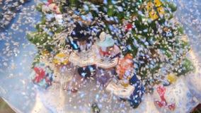 Weihnachtsglaskugel im Schnee mit Miniaturcharakteren singen Weihnachtslieder stock video