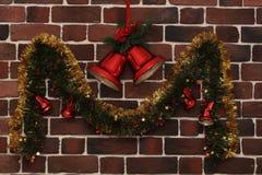 Weihnachtsglocken auf einer Backsteinmauer Stockfoto