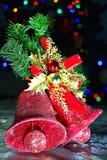 Weihnachtsglocken auf einer Kieferniederlassung mit Weihnachtslichthintergrund Stockfotografie