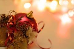 Weihnachtsglocken und -kugel mit Unschärfenhintergrund Stockbilder