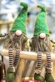 Weihnachtsgnomen in den grünen Kappen und in gestreiften Hosen Sitzen Sie auf einem hölzernen Schemel lizenzfreie stockfotografie