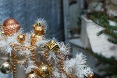 Weihnachtsgoldene Bälle, Spielwaren und weiße Girlandendekorationen Stockfotos