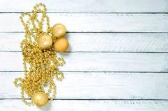 Weihnachtsgoldene Halskette und -bälle auf weißem hölzernem Hintergrund Nahaufnahme stockbild
