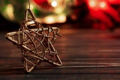 Weihnachtsgoldener Stern auf Hintergrund der Girlande beleuchtet auf schwarzem r Lizenzfreies Stockbild