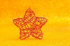 Weihnachtsgoldener Stern des Drahts über Goldenem stockfoto