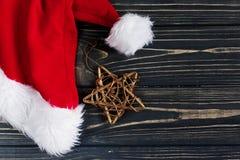 Weihnachtsgoldener Stern und Sankt-Hut auf stilvollem schwarzem rustikalem Holz Stockfoto