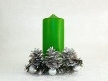 Weihnachtsgrüne Kerze, Kegel und Silberkugeln Stockfotografie
