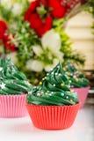 Weihnachtsgrüne kleine Kuchen mit festlichen Dekorationen Stockbild