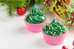 Weihnachtsgrüne kleine Kuchen mit festlichen Dekorationen Stockfotos