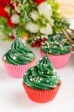Weihnachtsgrüne kleine Kuchen mit festlichen Dekorationen Stockbilder