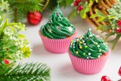 Weihnachtsgrüne kleine Kuchen mit festlichen Dekorationen Lizenzfreie Stockfotos