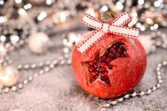Weihnachtsgranatapfel auf dem Tisch bedeckt mit Schnee Selektiver Fokus stockfotos