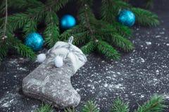 Weihnachtsgrauer Strumpf auf eingeschneitem schwarzem Hintergrund mit Blau Lizenzfreies Stockfoto