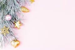 Weihnachtsgrenze mit Tannenzweigen, Nadelbaumkegeln, Weihnachtsbällen und goldenen Weihnachtsverzierungen auf Pastellhintergrund Stockfotos
