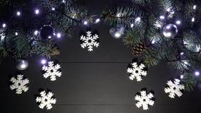 Weihnachtsgrenzrahmen mit Fichtenzweigen, unscharfen Blinklichtern, Weihnachtsbällen und Schneeflockenspielwaren auf einem schwar stock video footage