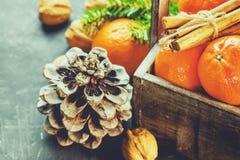 Weihnachtsgruß-Karten-Tangerine-Zimtstange-Tannen-Baumast-Kiefern-Kegel-Walnüsse im hölzernen Kasten Stockfoto